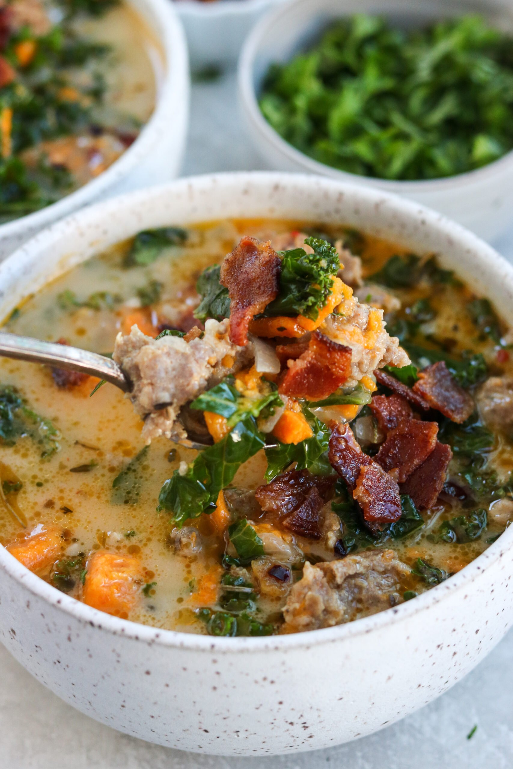 A spoonful of Whole30 Zuppa Toscana with crumbled bacon, sausage, and sweet potatoes
