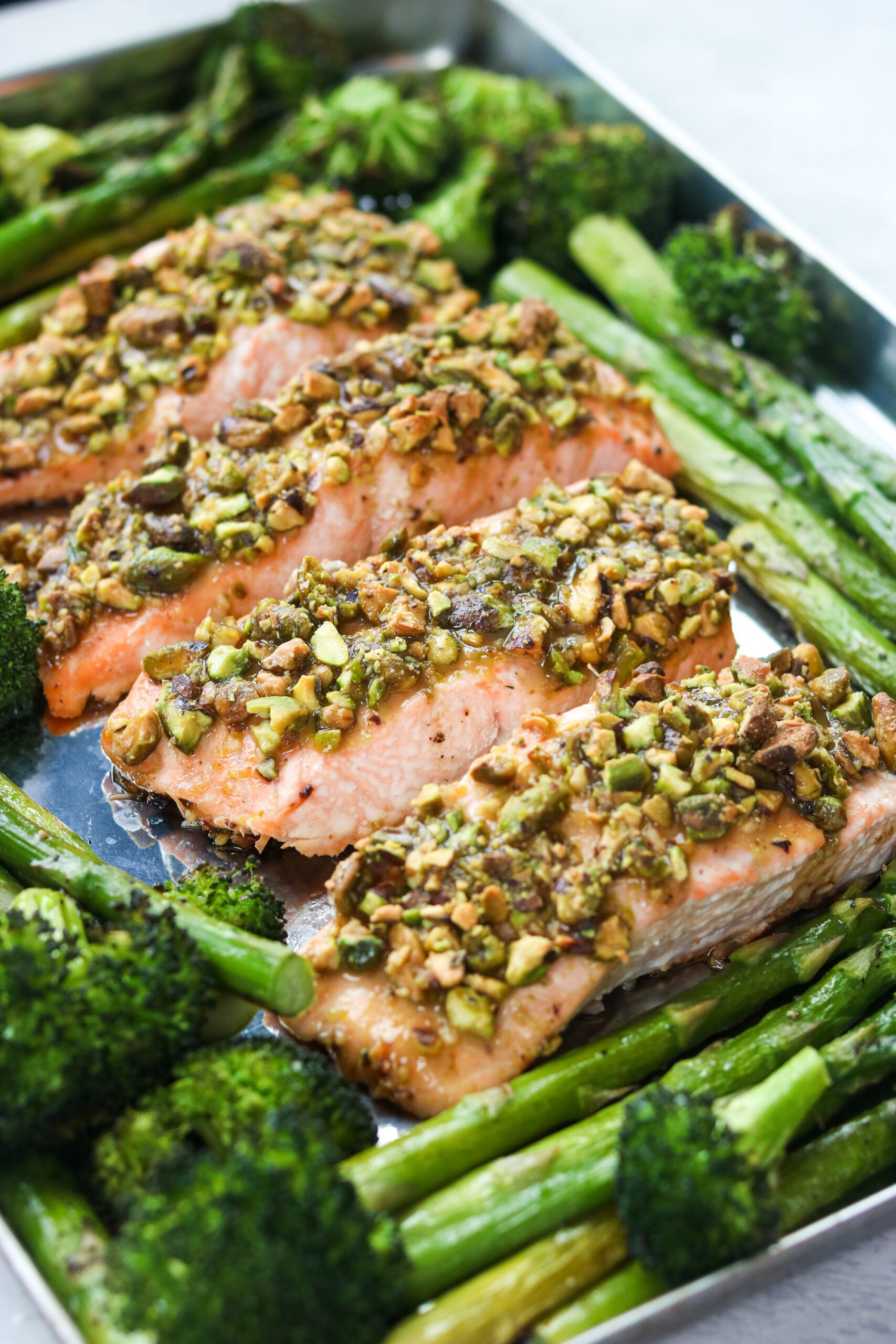 closeup of Crusted Salmon with Spring Veggies on a baking sheet