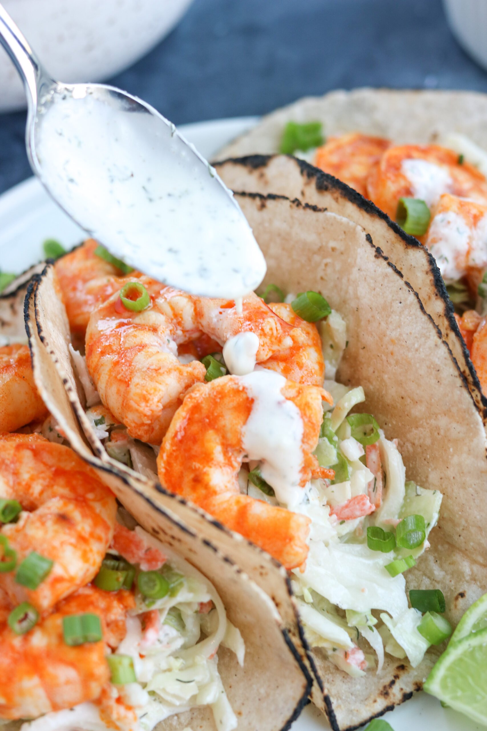 spoon adding sauce on a Paleo Buffalo Shrimp Tacos