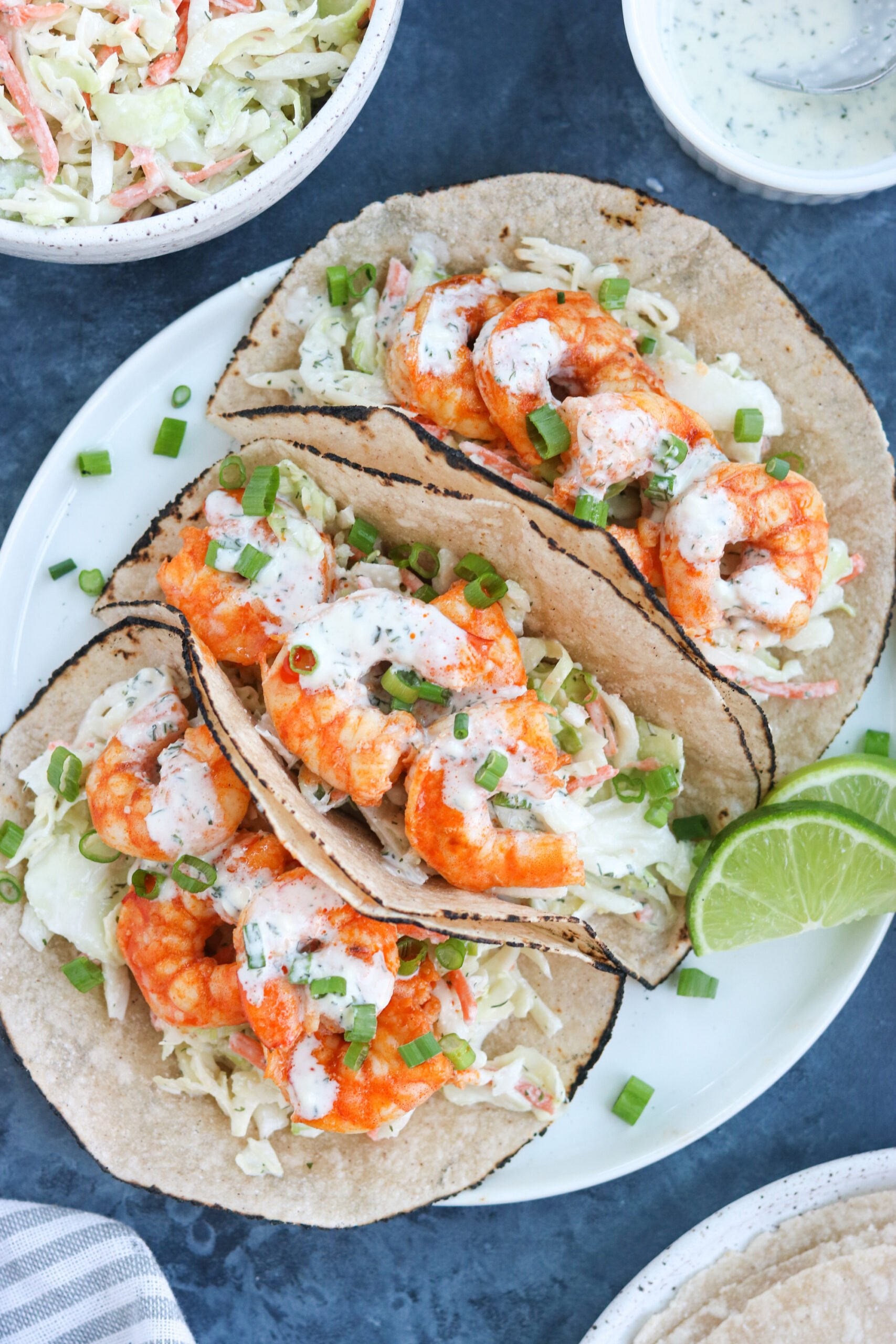 3 pieces of Paleo Buffalo Shrimp Tacos on a white plate with lemon on the side