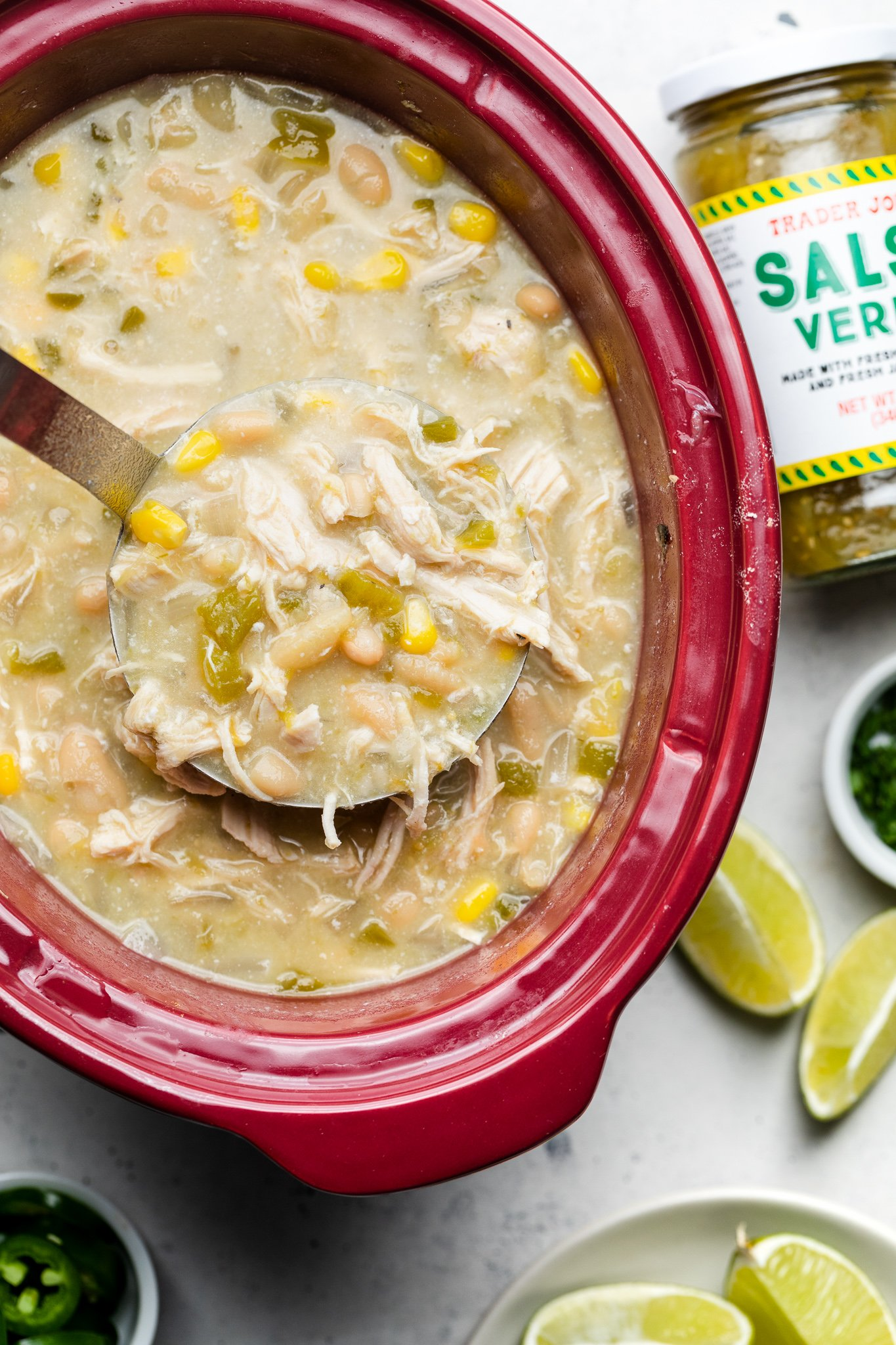 Slow Cooker Salsa Verde Chicken Chili on a red casserole