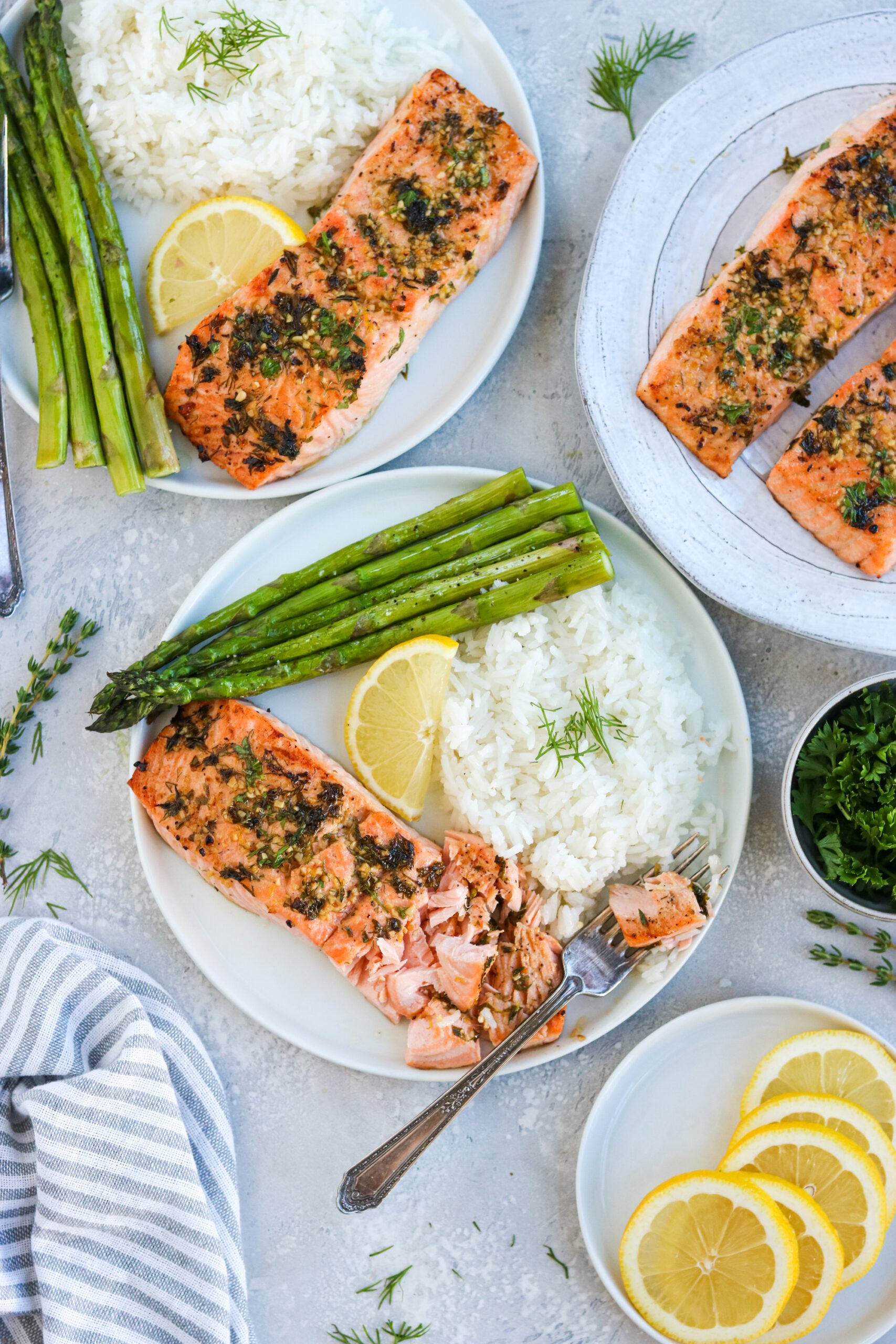 three plates of garlic herb baked salmon on a white plate with asparagus, white rice, and a lemon wedge, next to a silver fork with a white background
