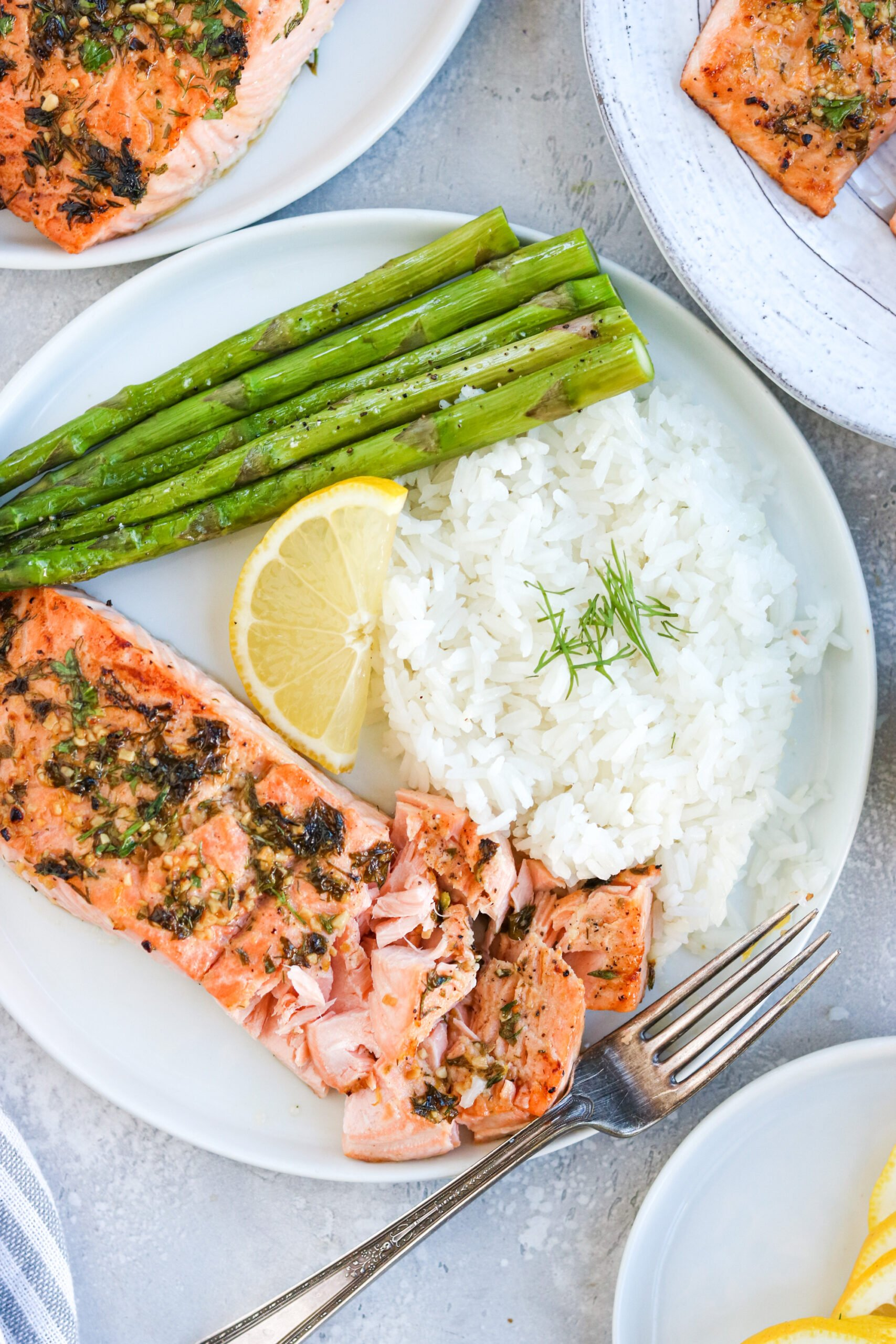 garlic herb baked salmon on a white plate with asparagus, white rice, and a lemon wedge, next to a silver fork with a white background