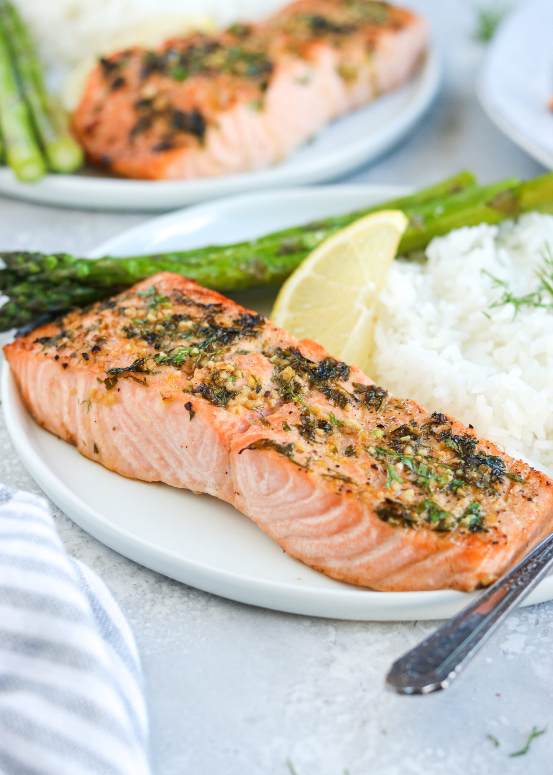 side view of garlic herb baked salmon on a white plate with asparagus, white rice, and a lemon wedge, next to a silver fork with a white background