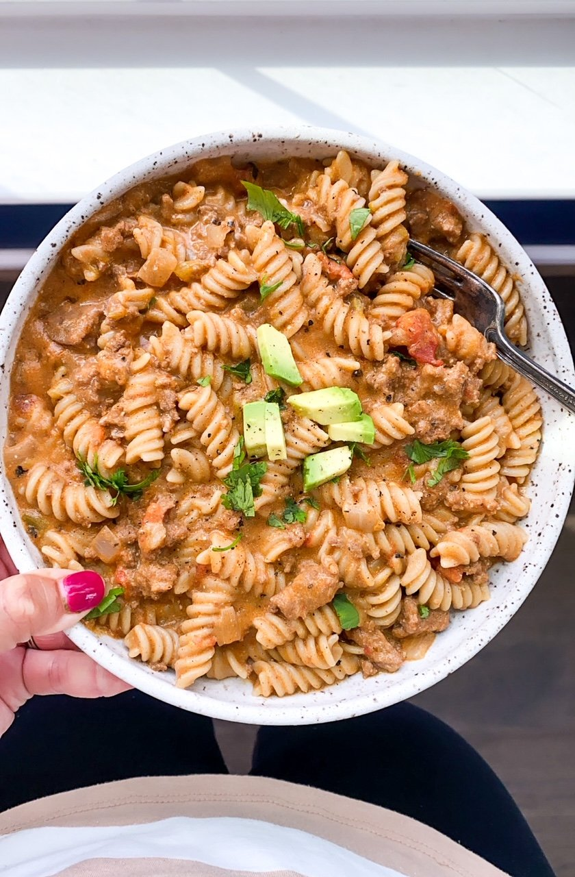 person holding a bowl of pasta