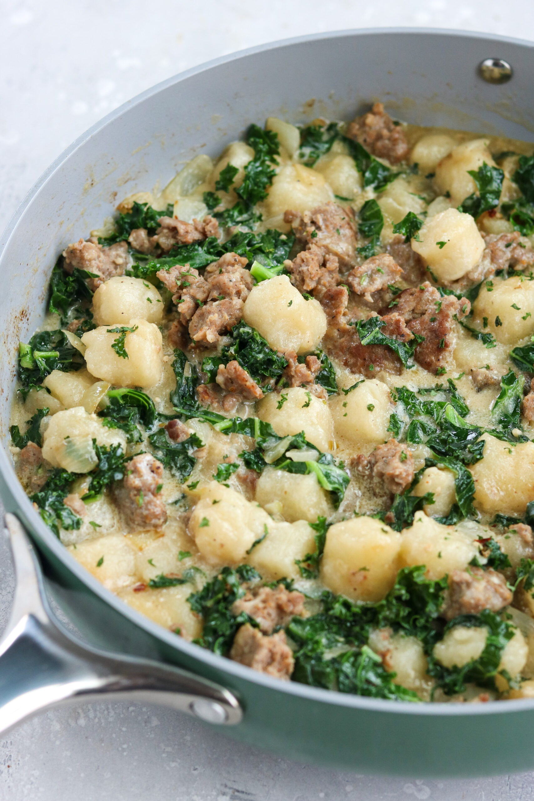 spinach kale gnocchi in a gray skillet with a silver handle with a white background