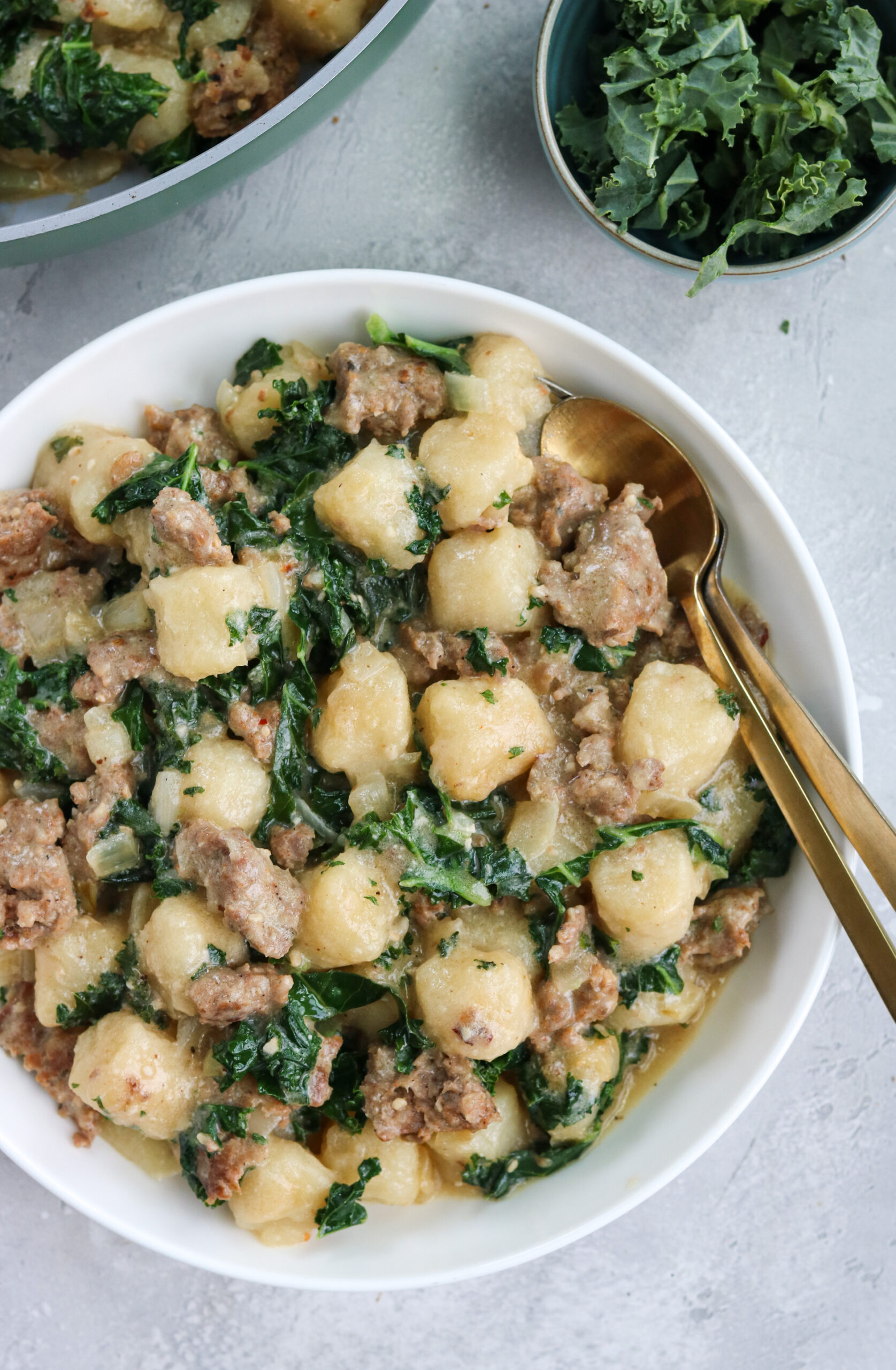a bowl of spinach kale gnocchi next to a bowl of kale and a skillet of spinach kale gnocchi with a white background