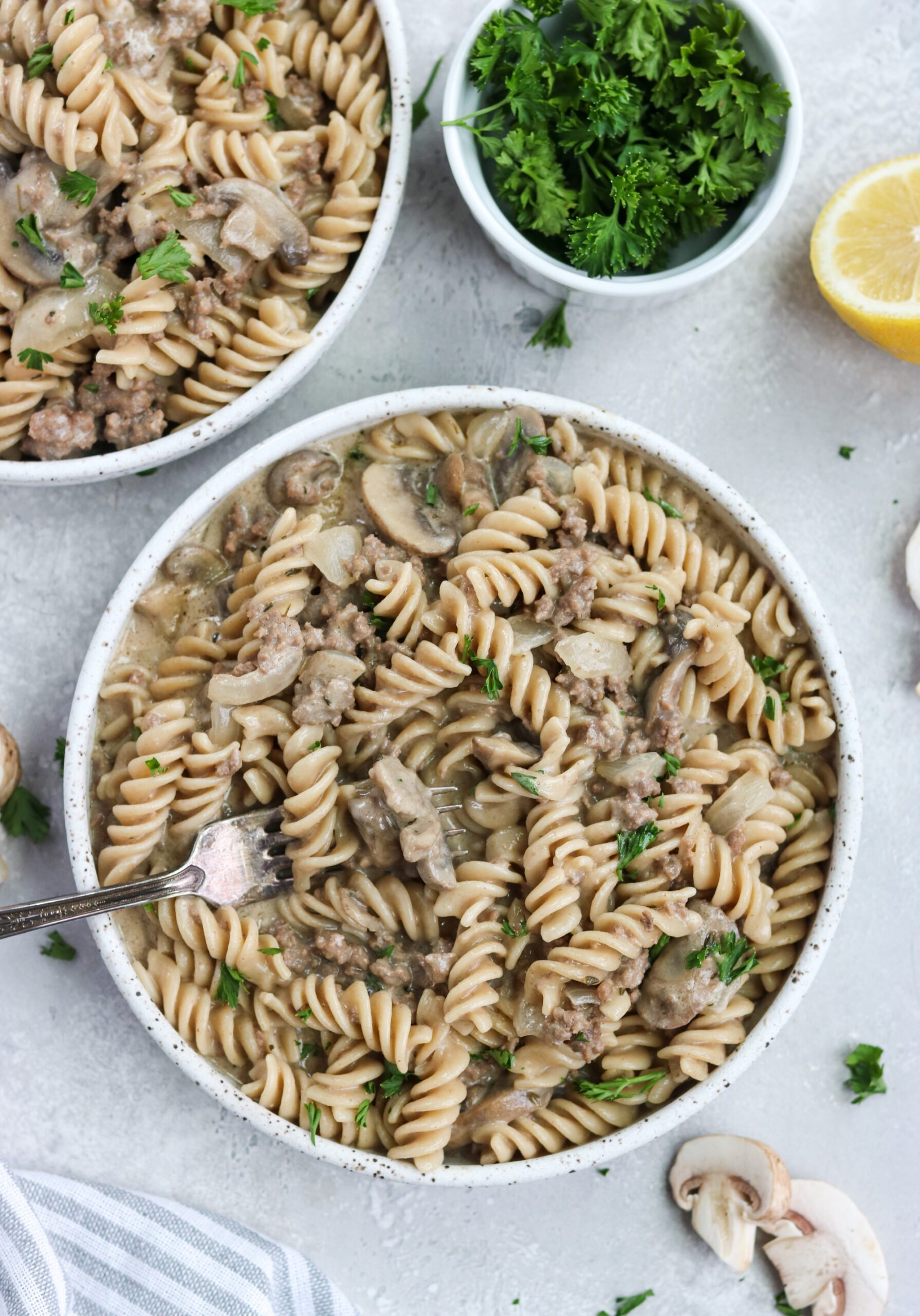overhead view of noodles in stroganoff sauce in two white bowls with an antique fork next to a pinch bowl of parsley and half a lemon