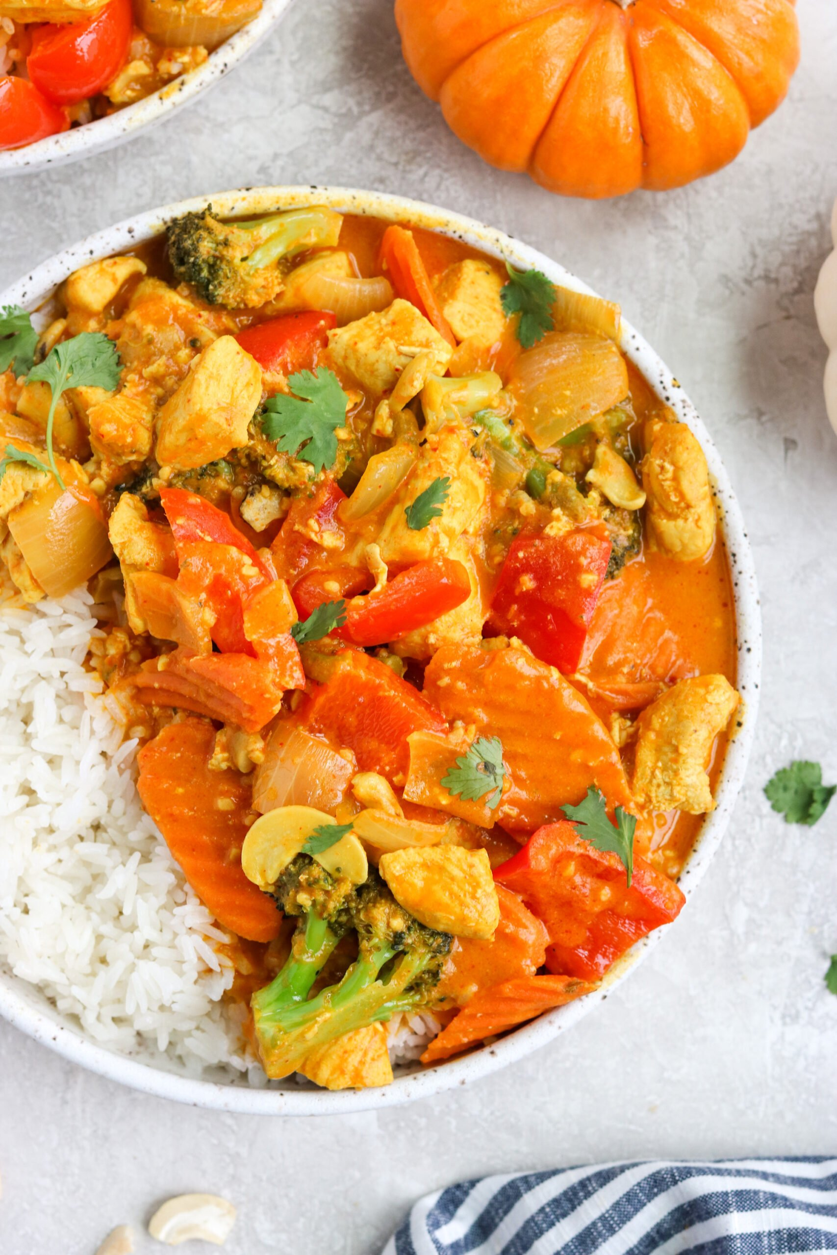 pumpkin curry chicken in a white speckled bowl with white rice with a white background